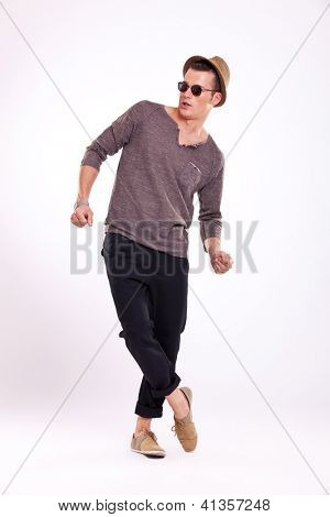 casual young man with sunglasses and hat acting surprised, looking to his side, on light background