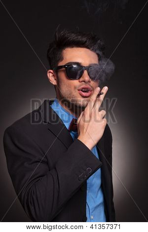portrait of a man wearing sunglasses and smoking a cigerette on black background