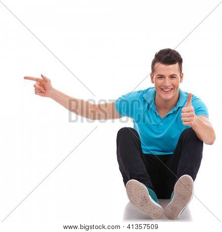 casual young man sitting on the floor and pointing to his side while looking at the camera and showing thumbs up sign. isolated on white