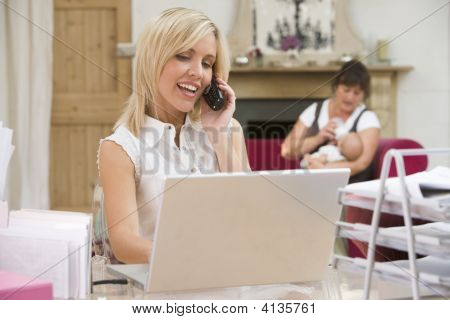 Woman In Home Office With Laptop And Telephone With Mother And Baby In Background