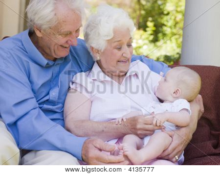 Großeltern im Freien auf der Terrasse mit Baby Lächeln