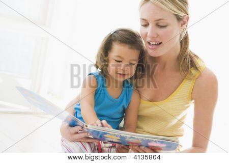 Madre e hija en el interior de lectura y sonriendo