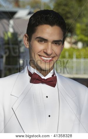 Portrait of a Hispanic groom in white tuxedo smiling on his wedding day