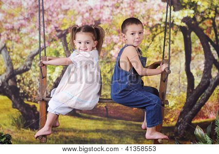 Two adorable preschoolers happily sitting on a rustic 2-person swing in a yard of blossoming trees.
