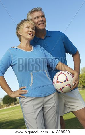 Low angle view of a happy Caucasian couple standing together with football in park