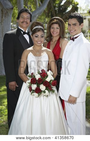 Portrait of a happy newlywed couple standing with friends at lawn