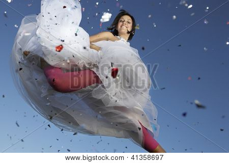 Portrait of a beautiful female in midair with colored paper sprinkled in foreground