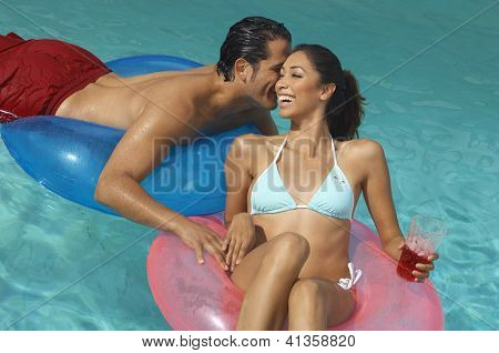 Happy couple having a good time on inflatable rings in swimming pool