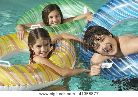 High angle view of three Caucasian friends enjoying together in swimming pool
