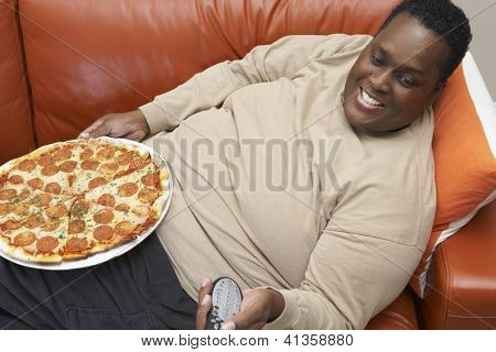 High angle view of an obese African American man watching television with pizza ob lap