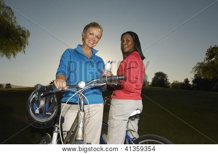 Low angle view of happy multiethnic female friends with bicycle