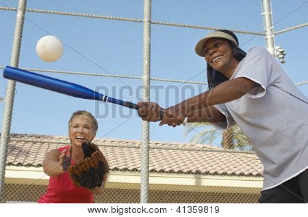 Low angle view of happy multi ethnic female friends playing baseball