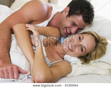 Couples Lying In Bed Laughing