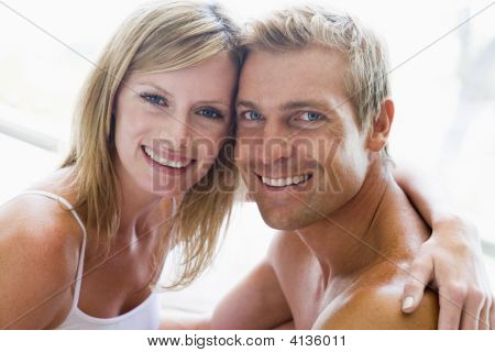Couples In Bedroom Embracing And Smiling