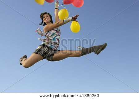 Portrait of a happy woman jumping with balloons against blue sky
