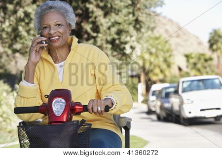 Portrait of an African American woman using cell phone on electric scooter