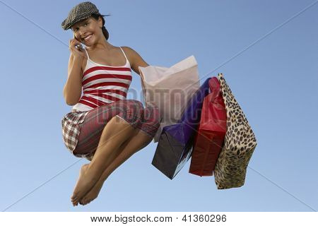 Full length of a woman with shopping bags using cell phone in midair against clear sky