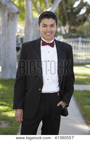 Portrait of a happy Hispanic groom in tuxedo standing at lawn on his wedding day