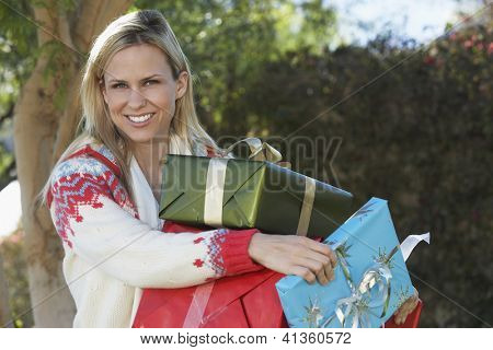 Portrait of a beautiful young woman carrying gift boxes at lawn