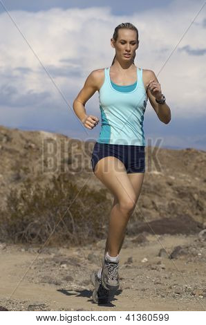 Full length of a beautiful woman jogging in mountains