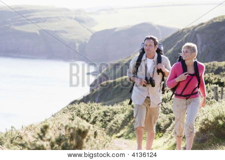 Couples On Cliffside Outdoors Walking And Smiling