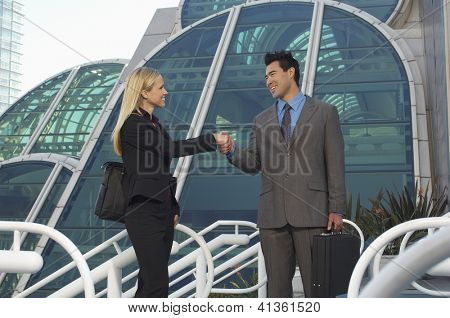 Business man and woman shaking hands in front of office building