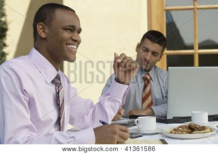 Two happy multi ethnic business people working at dinning table