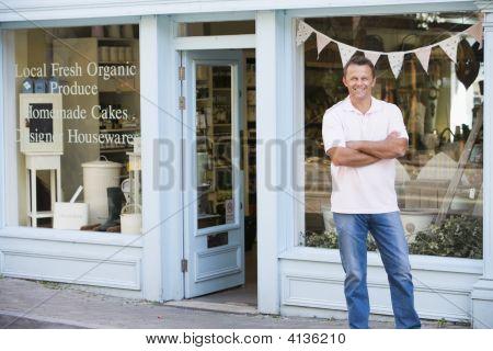 Hombre de pie delante de la tienda de alimentos orgánicos sonriendo