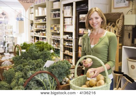 Woman In Market Looking At Potatoes Smiling