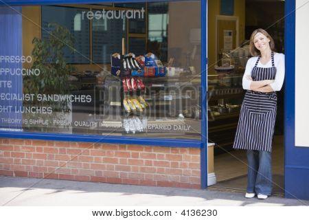 Mujer de pie en la puerta del restaurante sonriendo