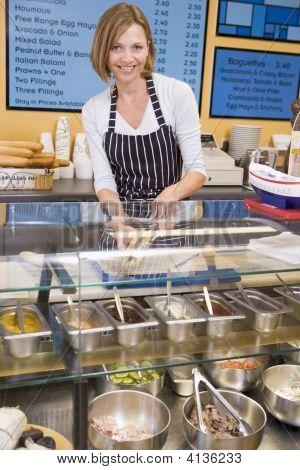 Mujer de pie en el mostrador en restaurante sonriendo
