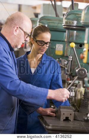 Two Machinists Working On Machine