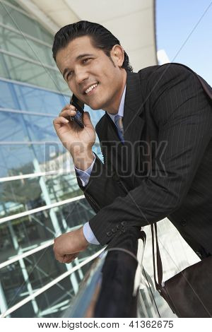 Handsome businessman using cell phone outside office building