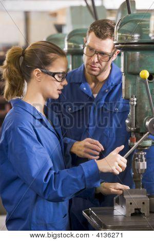 Dois mecânicos trabalhando na máquina