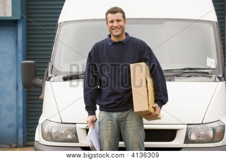 Deliveryperson Standing With Van Holding Clipboard And Box Smiling