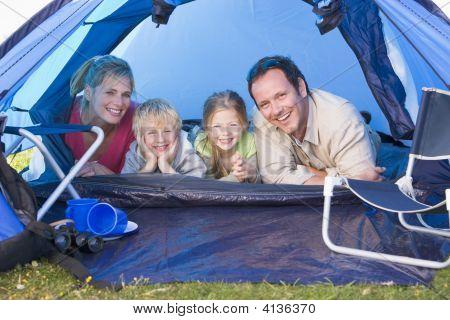 Familias acampando en tienda sonriendo