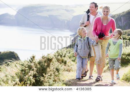 Familias caminando por el camino del acantilado agarrados de la mano y sonriendo