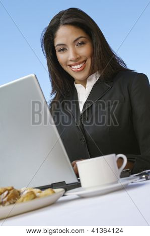 An African American businesswoman sitting with laptop and cup of tea