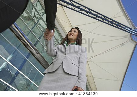 Low angle view of Asian businesswoman greeting male colleague in front of office