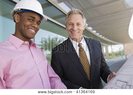 Portrait of a happy multi ethnic middle aged business man and architect standing with blue print