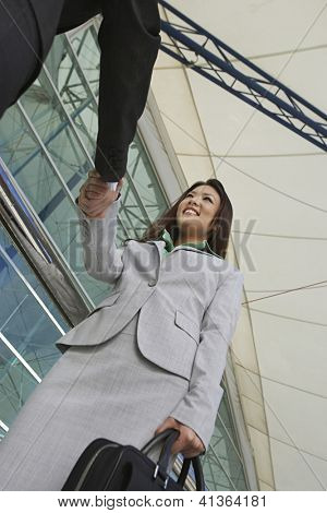 Low angle view of beautiful businesswoman greeting male colleague in front of office