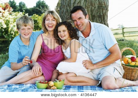 Families Sitting Outdoors With Picnic Smiling
