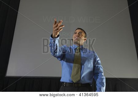 Low angle view of a happy businessman giving a lecture against projector screen