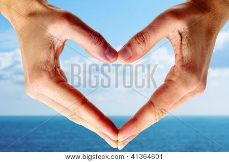 man hands forming a heart with the ocean and the sky in the background