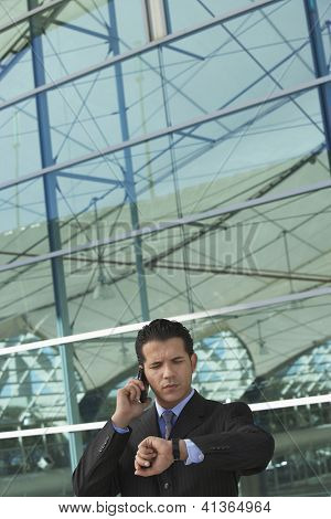 Businessman on call checking out the time outside office building