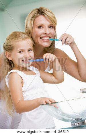 Woman And Young Girl In Bathroom Brushing Teeth