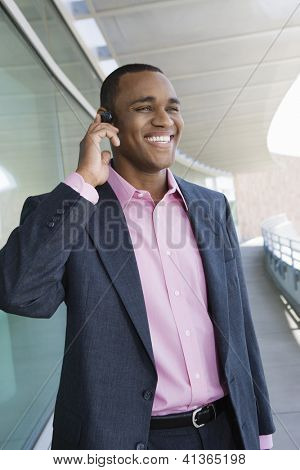 Happy successful business man using hands free device