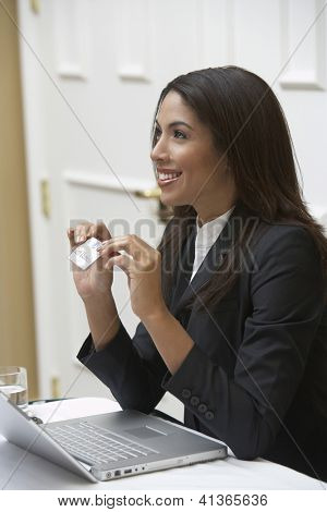 Side view of a friendly African American receptionist with laptop holding visiting card