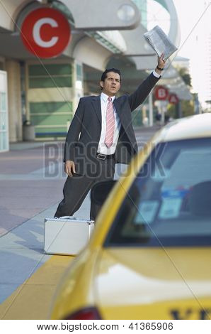 Businessman with briefcase and newspaper hailing taxi