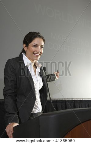Happy businesswoman giving a lecture at podium